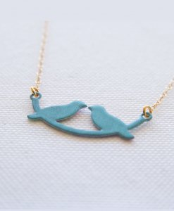 A lovebird necklace on a little turquoise swing